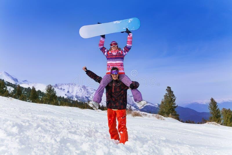 Счастливый snowboarder с женщиной на его плечах стоковая фотография