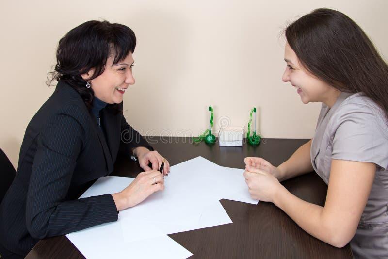 2 счастливых дамы дела сидя в офисе стоковое изображение