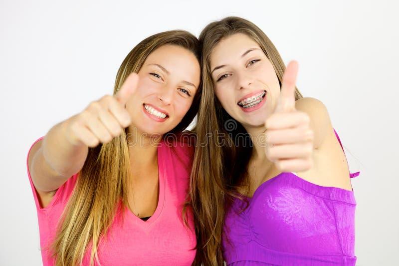 2 счастливых девушки показывая большой палец руки вверх по чувствовать счастливый стоковые изображения