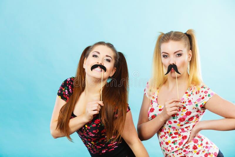 2 счастливых женщины держа поддельный усик на ручке стоковые фотографии rf