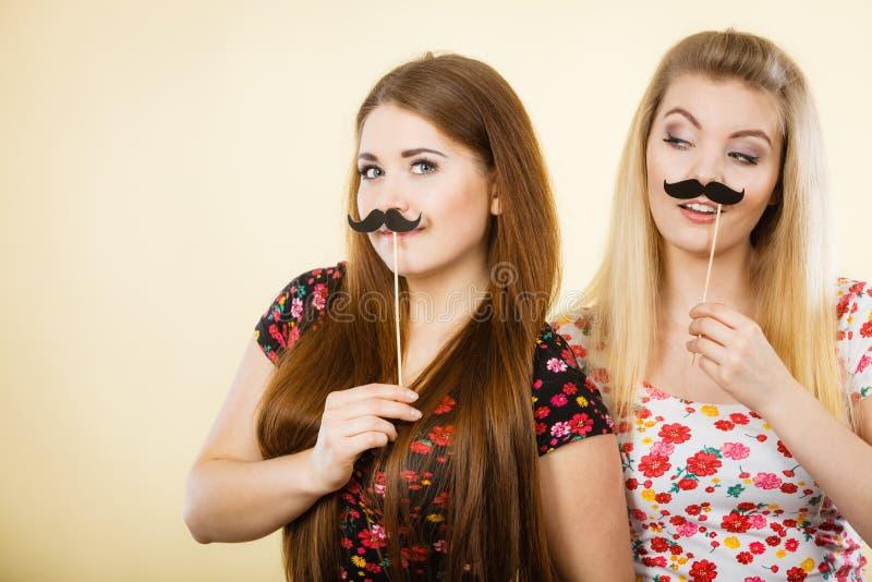 2 счастливых женщины держа поддельный усик на ручке стоковое фото