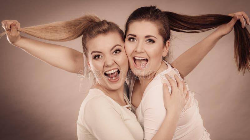 2 счастливых женщины друзей обнимая держащ волосы стоковые изображения