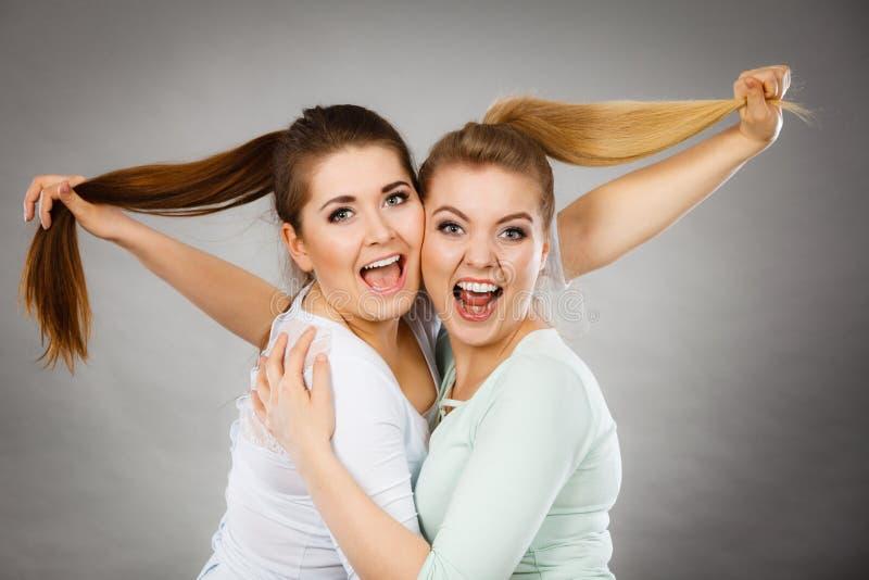2 счастливых женщины друзей обнимая держащ волосы стоковое фото