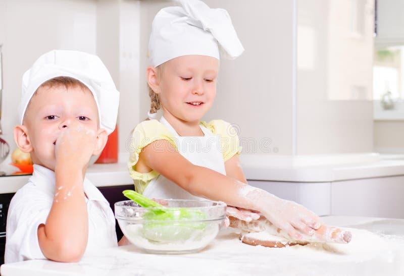 2 счастливых маленького ребенка уча испечь стоковое фото rf