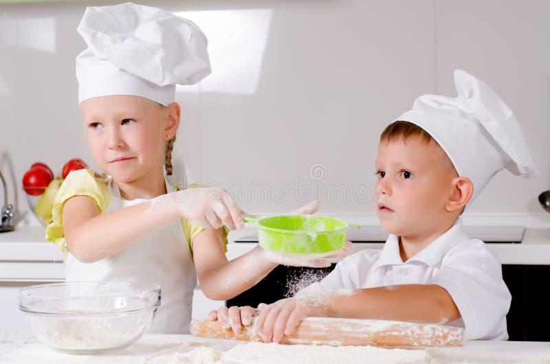 2 счастливых маленького ребенка уча испечь стоковая фотография rf