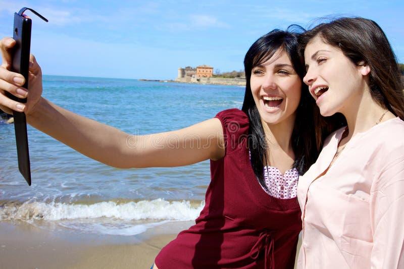 2 счастливых молодой женщины принимая selfie усмехаясь на пляже стоковые фотографии rf