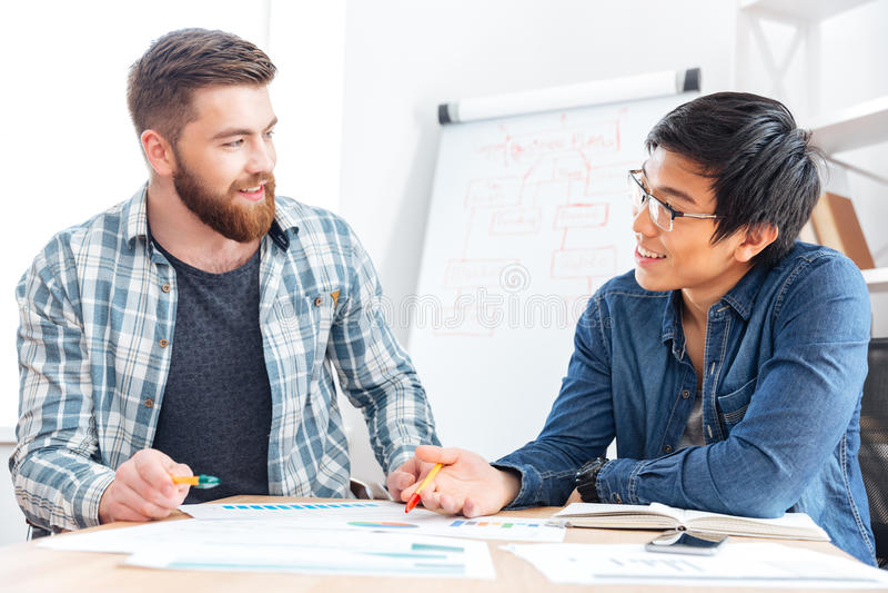 2 счастливых молодых бизнесмена работая совместно в офисе стоковые фото