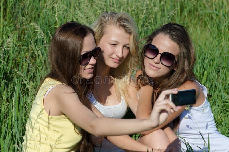 3 счастливых молодых подруги делая selfie телефоном стоковое фото