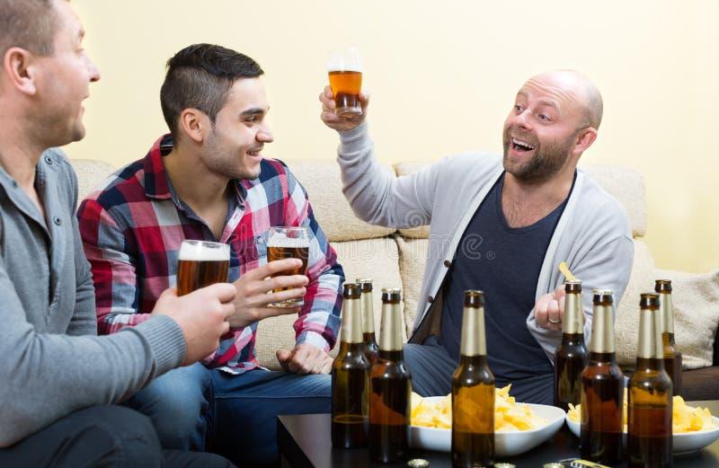 3 счастливых друз выпивая пиво стоковая фотография
