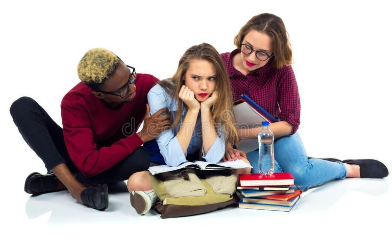 3 счастливых студента сидя с книгами, компьтер-книжкой и сумками стоковые фото
