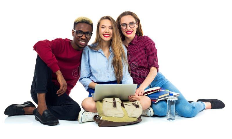3 счастливых студента сидя с книгами, компьтер-книжкой и сумками стоковые изображения