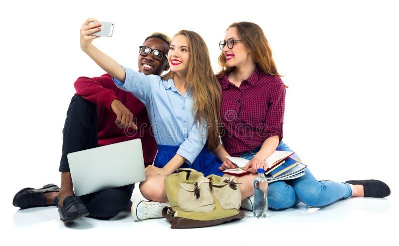 3 счастливых студента с книгами, компьтер-книжкой, кладут в мешки и делают selfie стоковая фотография