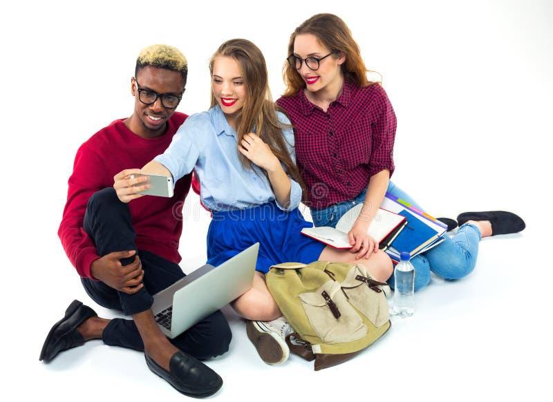 3 счастливых студента с книгами, компьтер-книжкой, кладут в мешки и делают selfie стоковое изображение