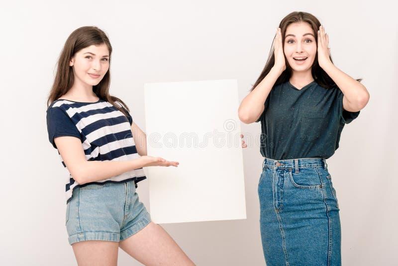 2 счастливых усмехаясь молодой женщины заботя большой пустой шильдик стоковое изображение