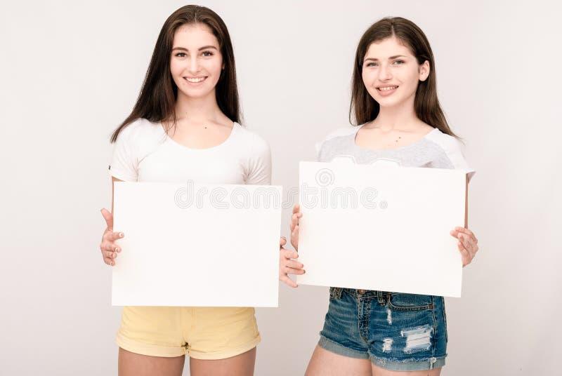 2 счастливых усмехаясь молодой женщины заботя большой пустой шильдик стоковое фото rf