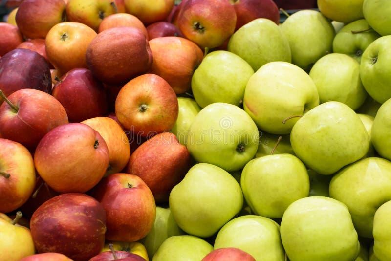 Счетчик с красными и зелеными яблоками на рынке стоковое изображение