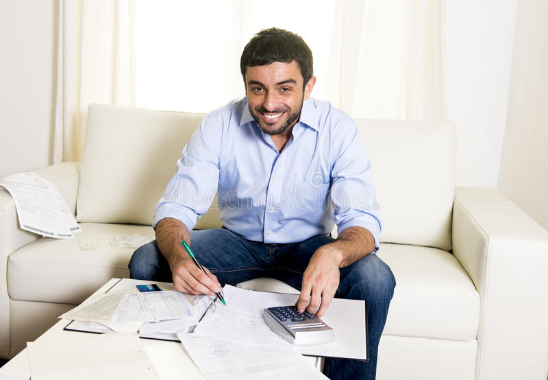 Счеты и кредитная карточка счастливого латинского человека оплачивая на софе стоковое фото rf