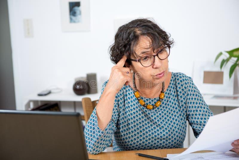 Счеты старшей женщины оплачивая с компьтер-книжкой дома стоковая фотография