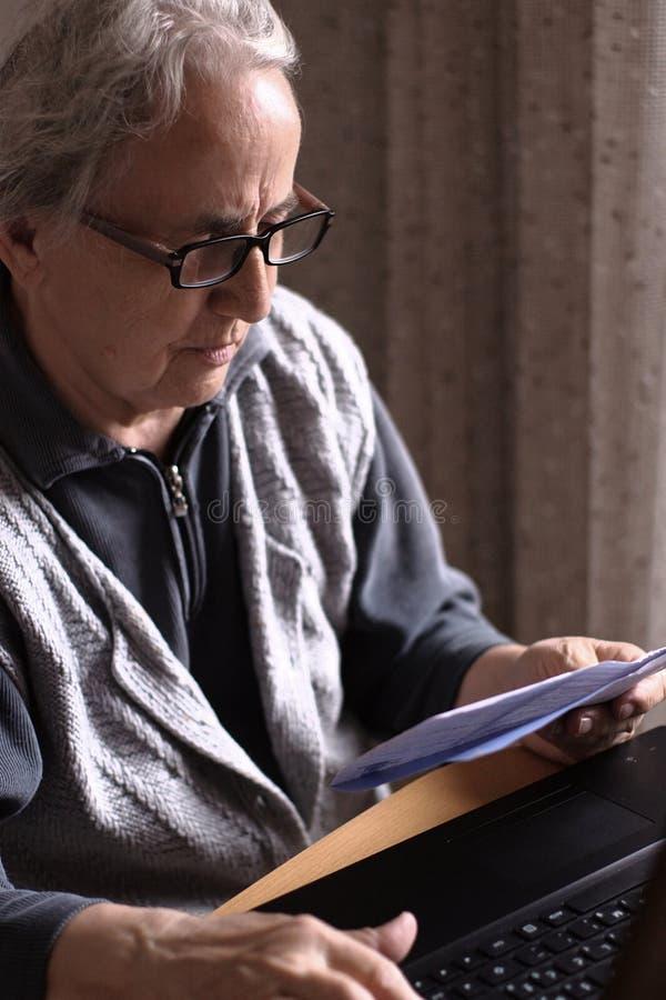 Счеты старшей женщины оплачивая с компьтер-книжкой стоковая фотография