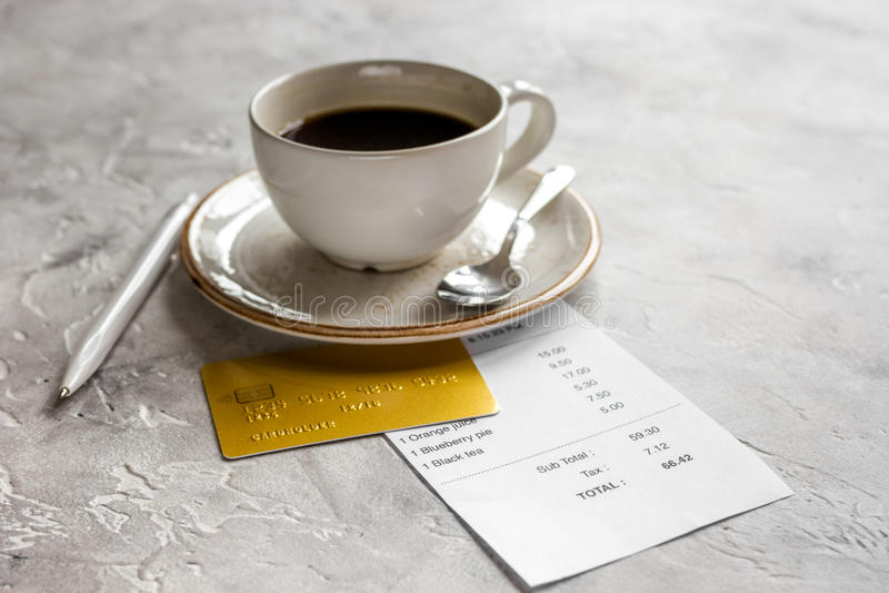 Счет кофе и получения для оплаты кредитной карточкой на каменной предпосылке таблицы стоковые изображения