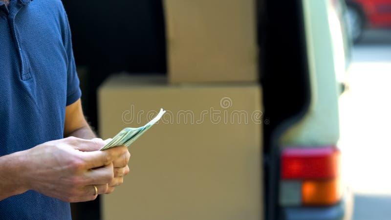 Считать работника заработал доллары и закрывая коробки фургона двери, транспортировать товаров стоковое изображение rf