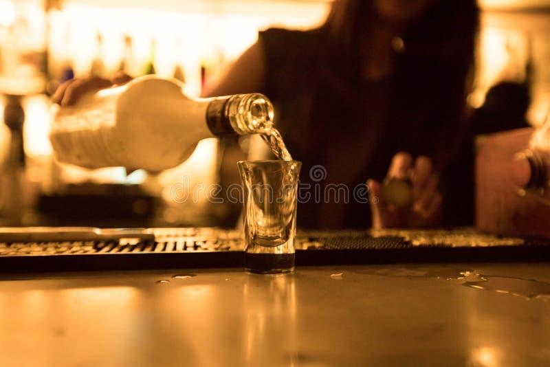 Съемка бармена лить спирта на баре стоковые изображения rf