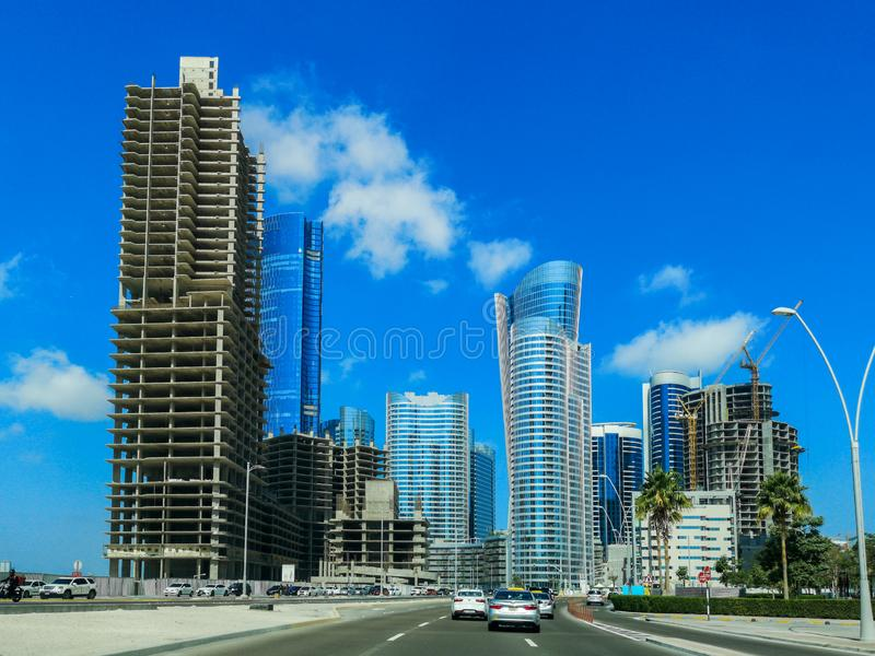 Съемка башен, ландшафта, небоскребов и строительных площадок острова Reem Al известных на ясном голубом небе в городе Абу-Даби стоковая фотография
