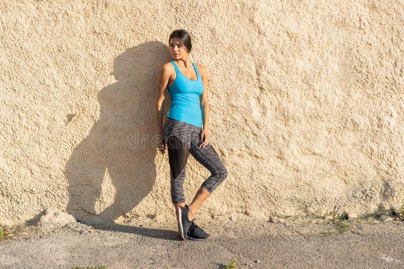 Съемка бегуна пригонки стоя против стены outdoors Sporty женщина ослабляя после идущей тренировки стоковое фото rf