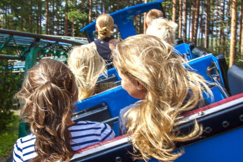 Съемка вид сзади молодые люди на захватывающей езде русских горок на парке атракционов с нерезкостью движения группа потехи друзе стоковое изображение rf