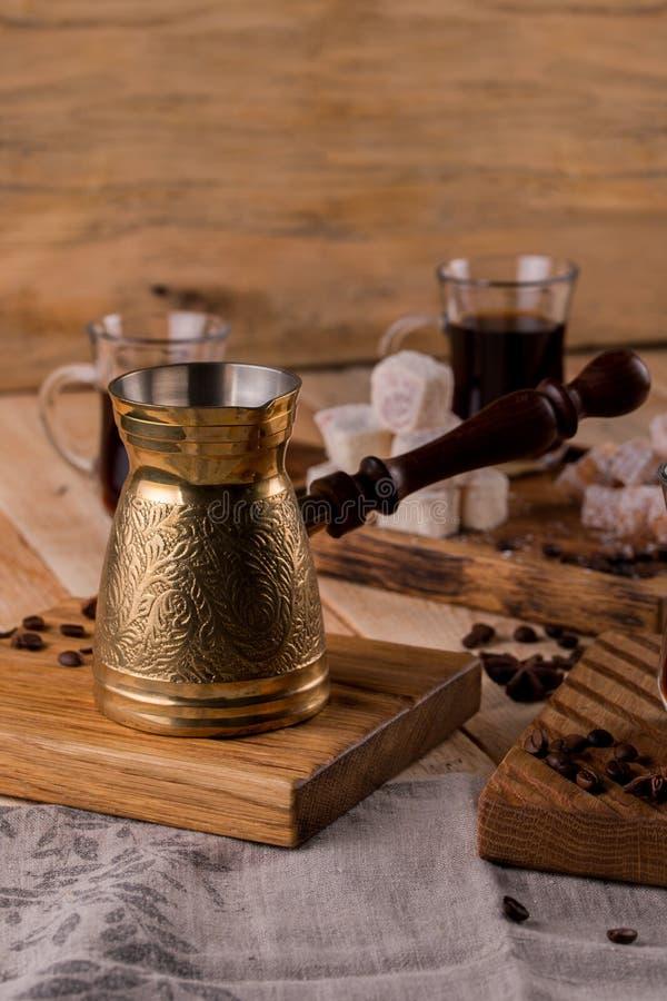 съемка конца-вверх чашки кофе с зажаренными в духовке фасолями и cezve Турецкий кофе в традиционный выбитый турка металла стоковое фото rf
