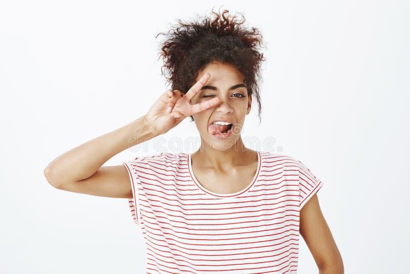 Съемка конца-вверх ougoing уверенно молодая женщина в striped футболке, показывающ победу или жест мира над глазом, подмигивая стоковое фото