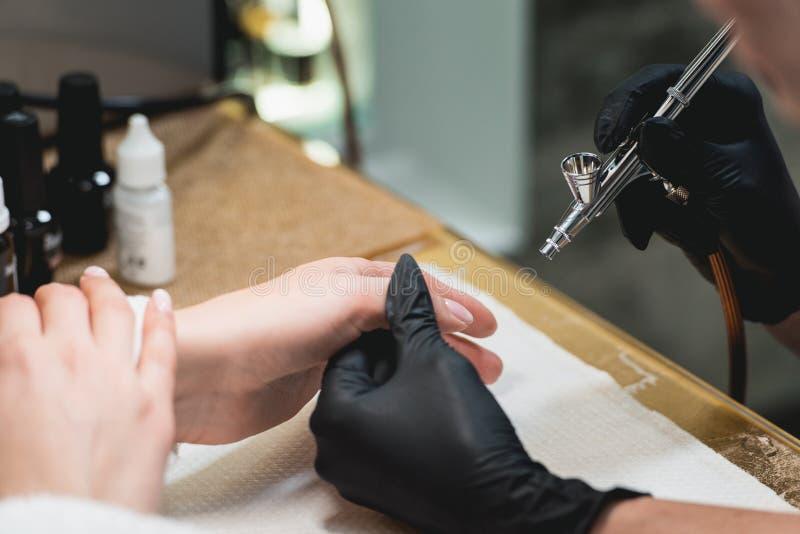 Съемка крупного плана женщины в салоне ногтя получая маникюр beautician с airbrush Женщина получая маникюр ногтя стоковая фотография
