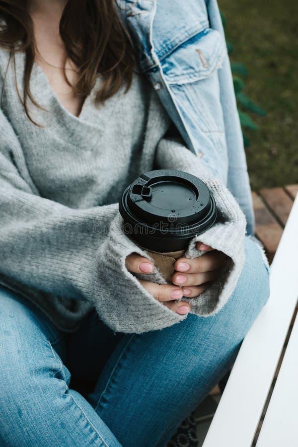 Съемка образа жизни безликая женщины в сером свитере держа чашку с горячим питьем снаружи стоковое изображение