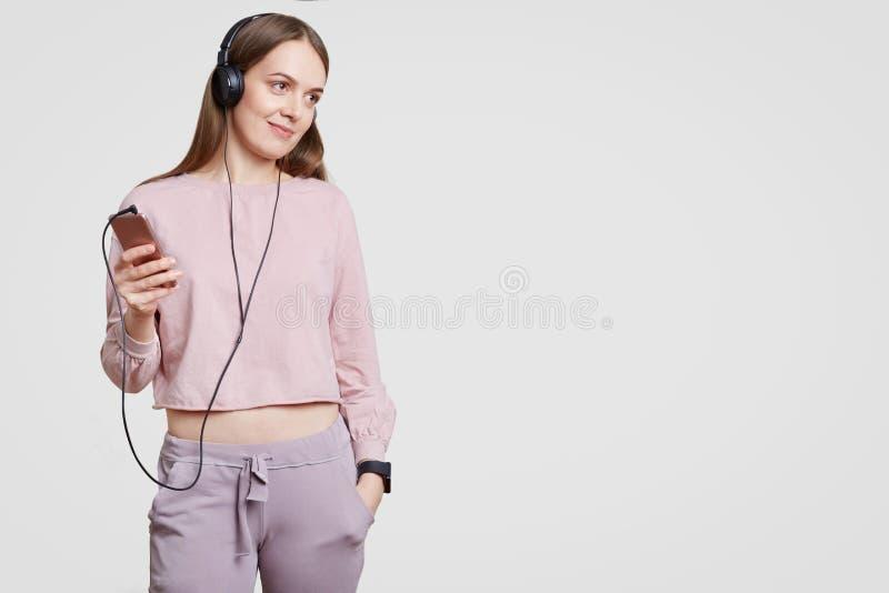 Съемка студии довольной привлекательной женщины одетой в вскользь одеждах, держит руку в pcket, держит современное электронное ус стоковые фотографии rf