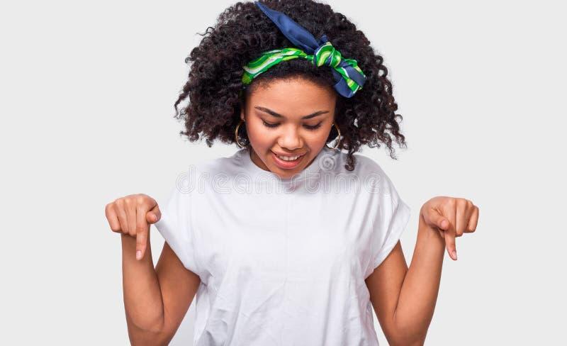 Съемка студии довольно молодого Афро-американского пункта женщины на поле, нося белой футболке, красочном держателе, стене ont бе стоковое изображение