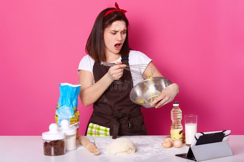 Съемка студии женщины юркнуть яйца в кухне, удивляла выражение лица, делающ домодельное печенье, печь торты, стоит близко стоковая фотография rf