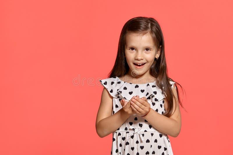 Съемка студии конца-вверх красивой маленькой девочки брюнета представляя против розовой предпосылки стоковые изображения