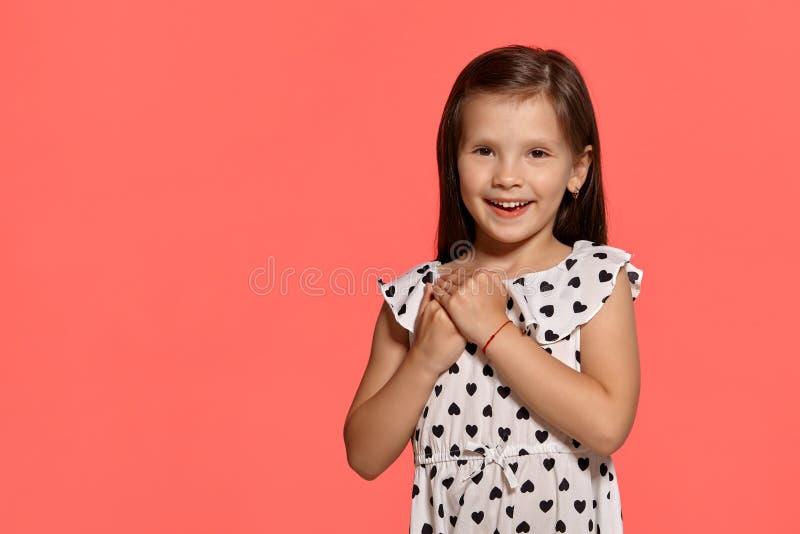 Съемка студии конца-вверх красивой маленькой девочки брюнета представляя против розовой предпосылки стоковое фото rf