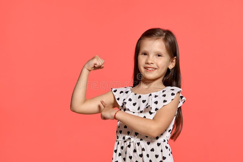 Съемка студии конца-вверх красивой маленькой девочки брюнета представляя против розовой предпосылки стоковое изображение
