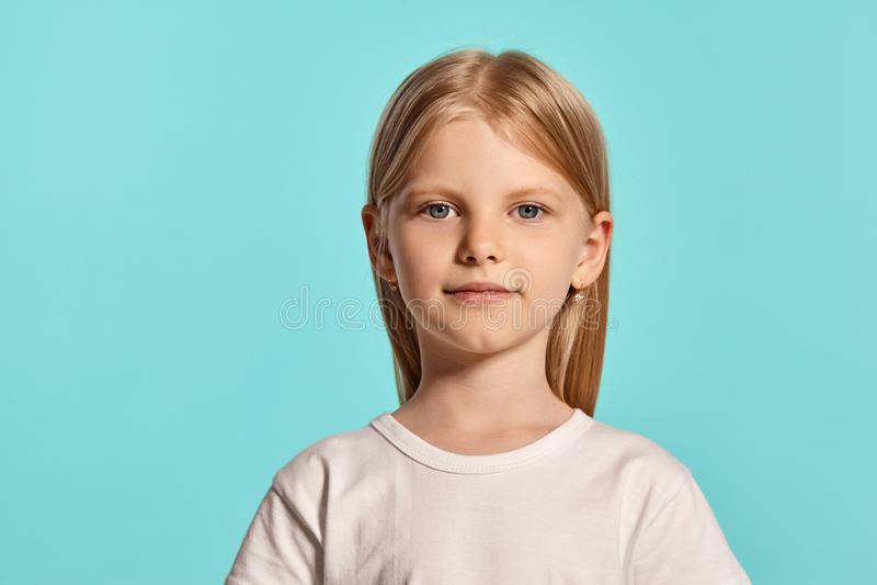 Съемка студии конца-вверх прекрасной белокурой маленькой девочки в белой футболке представляя против голубой предпосылки стоковые фотографии rf