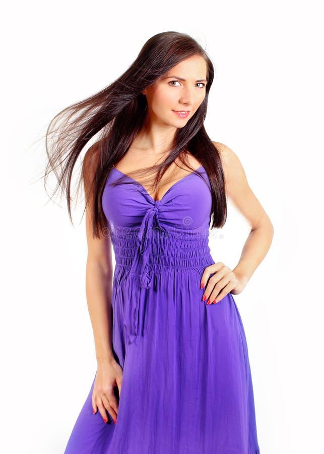 Съемка студии молодой женщины в фиолетовом платье с ветром в ее волосах стоковое изображение
