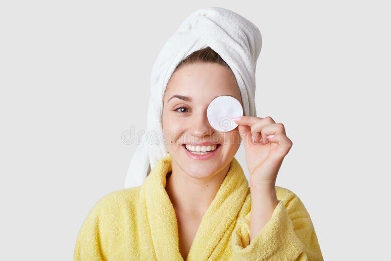 Съемка студии приятной выглядя молодой усмехаясь европейской женщины покрывает глаз с диском хлопка, имеет белое полотенце на гол стоковые фото