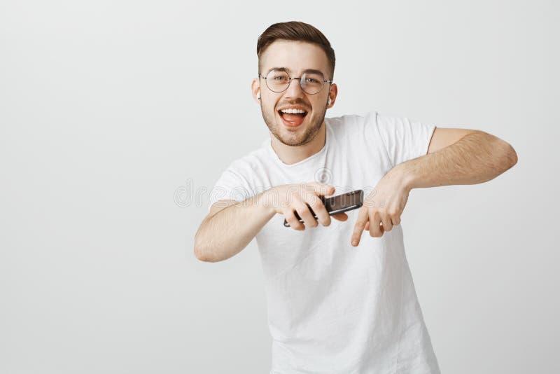 Съемка студии счастливой красивой и беспечальной молодой мужской модели в белой футболке поя вдоль любимой песни делая рэп стоковые изображения