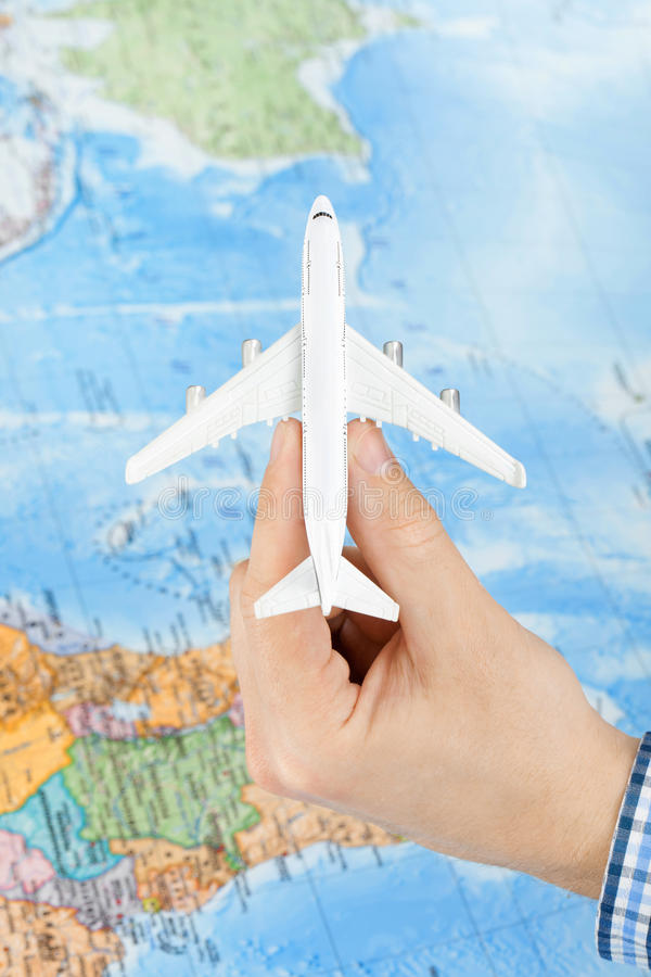 Съемка студии самолета игрушки в руке с картой мира на предпосылке - путешествовать концепция стоковое фото rf