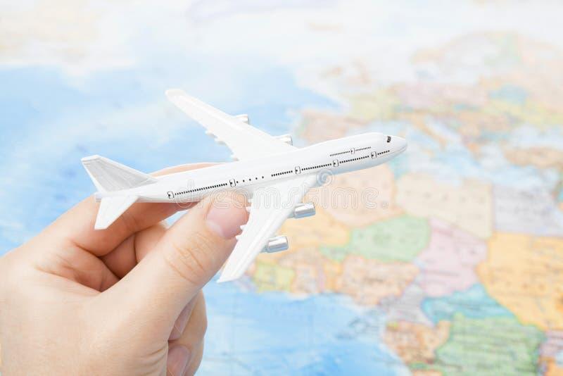 Съемка студии самолета игрушки в руке с картой мира на предпосылке - сфокусируйте на самолете стоковые фото