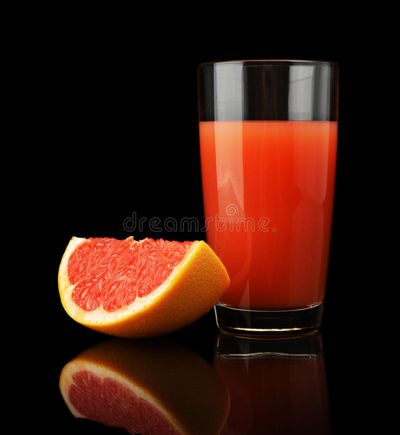 Съемка студии сока и квартала грейпфрута изолированных на черноте стоковая фотография