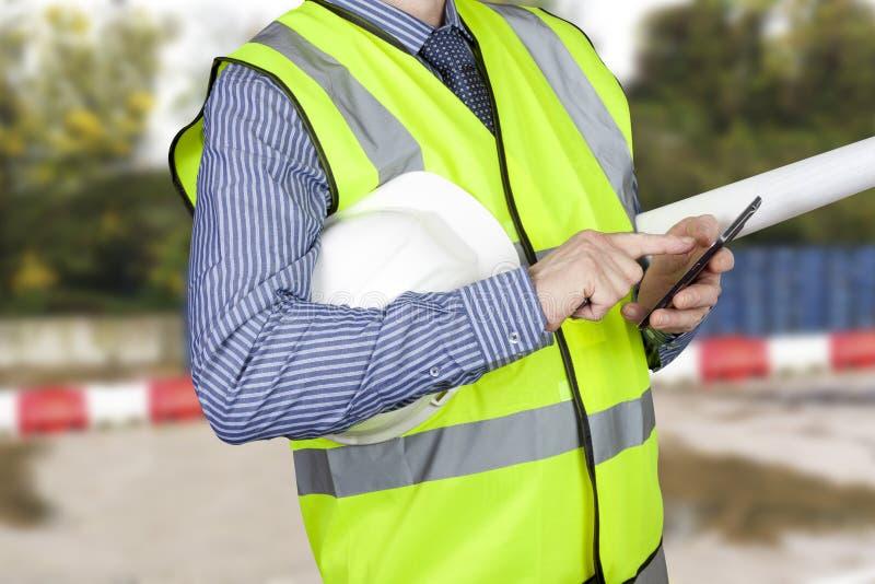 Съемщик здания в высоком vis с планами места проверяя его умный телефон стоковое изображение rf