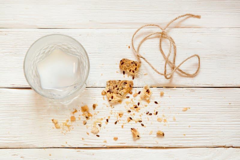 Съеденные печенья и пьяное молоко с шишками на белом деревянном backg стоковые фотографии rf