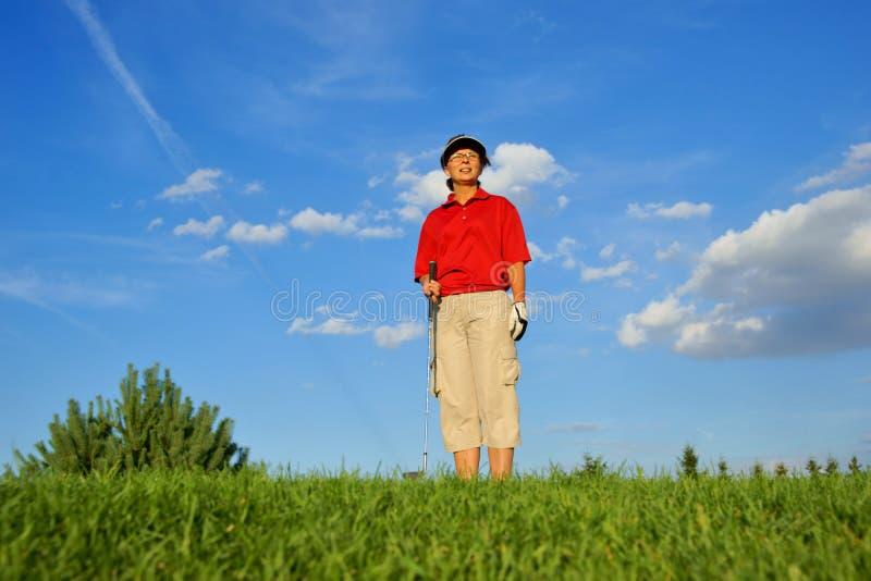 Сыграйте в гольф, игрок в гольф женщины наблюдающ полетом шарика стоковая фотография rf