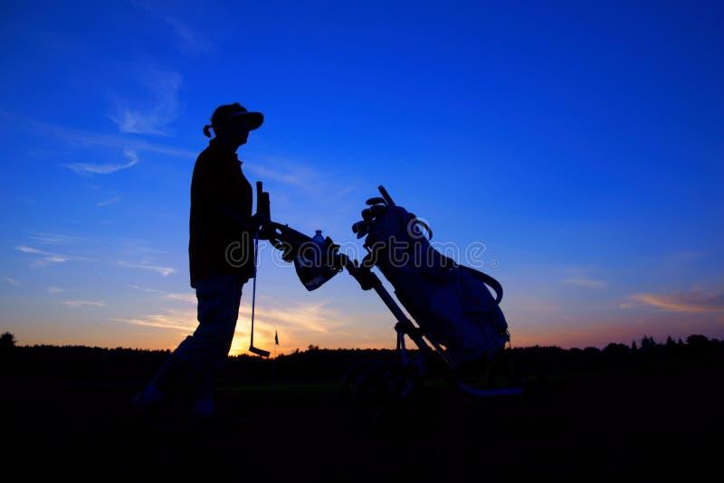 Сыграйте в гольф, игрок в гольф женщины с сумкой гольфа на заходе солнца, как предпосылки стоковая фотография